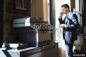 Caucasian businessman talking on cell phone near window